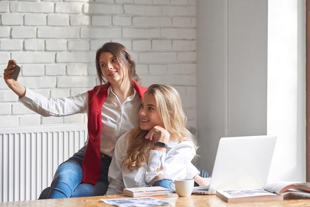 Twee mooie jonge vriendinnen nemen selfies samen in het café met behulp van slimme telefoon copyspace vriendschap mensen tieners jeugd technologie herinneringen emoties saamhorigheid hechting.