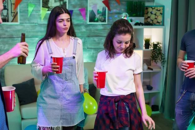 Twee mooie jonge vrouw dansen op een feestje met hun vrienden.