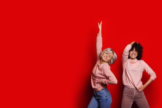 Twee mooie jonge vrouw gekleed in roze shirts dansen tegen rode studio muur.
