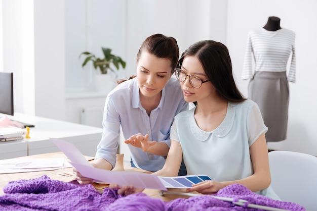 Twee mooie jonge vrouwelijke kleermakers zitten aan de tafel en kijken door kleurenschema's, in een poging een juiste keuze te maken.