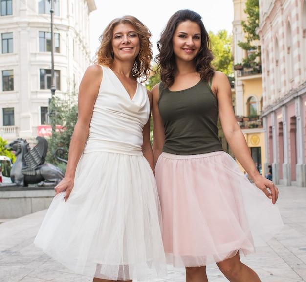 Twee mooie jonge vrouwelijke vriendinnen in de stad