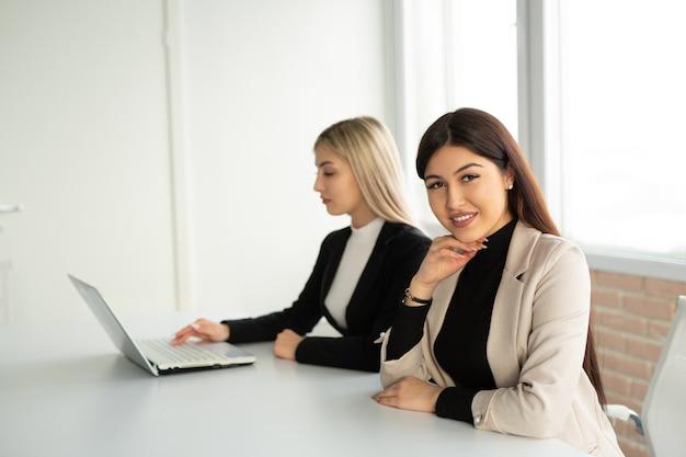 Twee mooie jonge vrouwen aan de tafel in het kantoor met een laptop