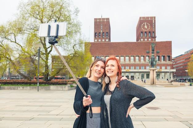 Twee mooie jonge vrouwen die een selfie in oslo nemen