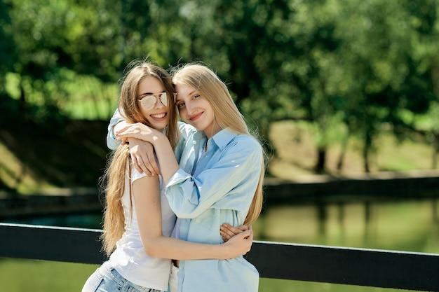 Twee mooie jonge vrouwen die elkaar omhelzen