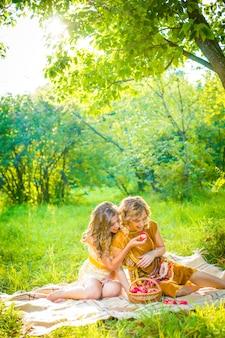 Twee mooie jonge vrouwen die gele en bruine kleding met boek en mand van appelen dragen bij picknick in park
