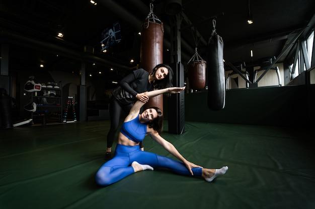 Twee mooie jonge vrouwen die geschiktheid in een gymnastiek doen