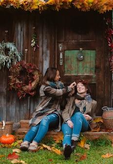 Twee mooie jonge vrouwen, die hun gezichten behandelen met een geel de herfstblad, die op een oude houten achtergrond glimlachen.