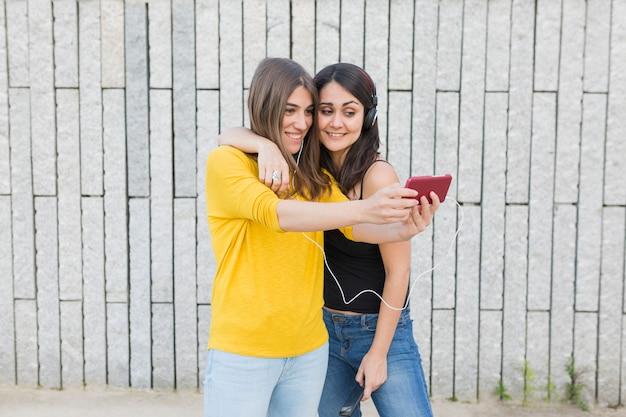 Twee mooie jonge vrouwen die pret hebben in openlucht. een foto maken met een mobiele telefoon en naar muziek luisteren. casual kleding. stad achtergrond. levensstijl buitenshuis