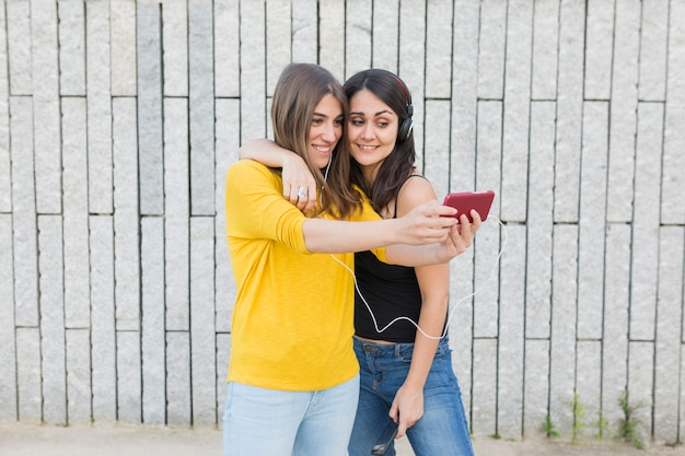 Twee mooie jonge vrouwen die pret hebben in openlucht. een foto maken met een mobiele telefoon en naar muziek luisteren.