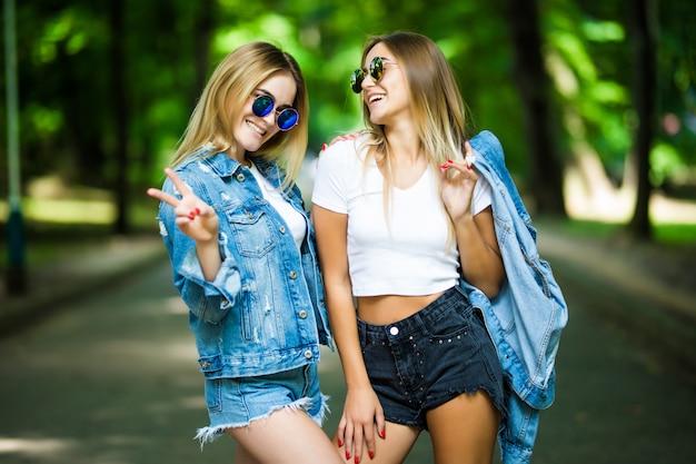 Twee mooie jonge vrouwen die pret in de stad hebben