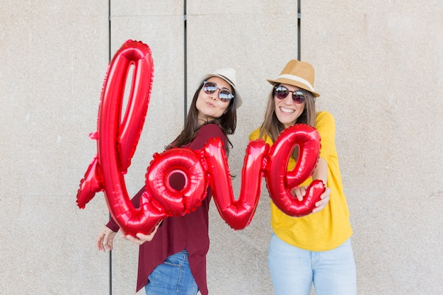 Twee mooie jonge vrouwen die pret in openlucht met een rode ballon met een vorm van het liefdewoord hebben. casual kleding. ze dragen hoeden en moderne zonnebrillen. levensstijl buitenshuis