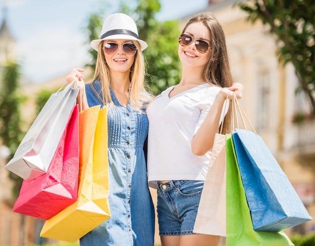 Twee mooie jonge vrouwen die van winkelen genieten.