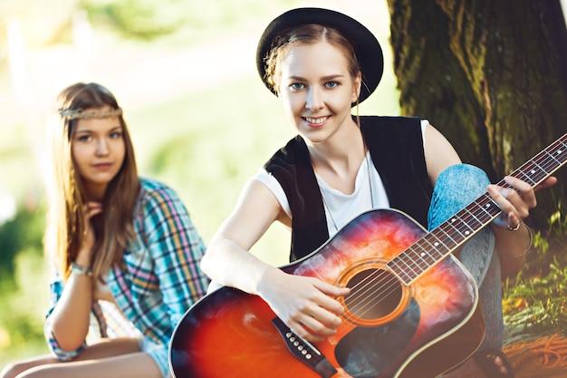 Twee mooie jonge vrouwen gitaarspelen op een picknick