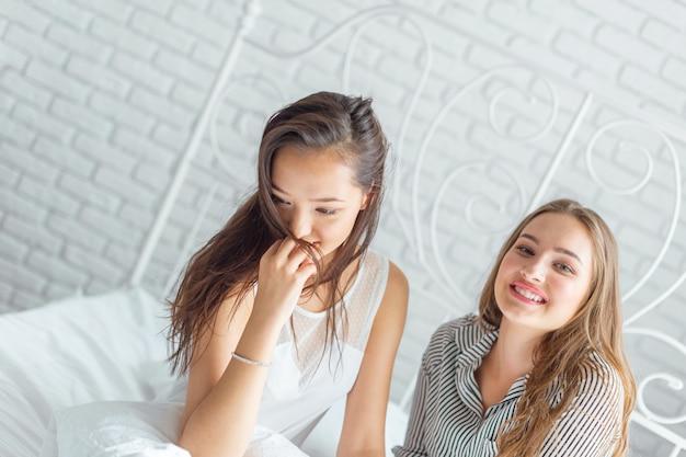 Twee mooie jonge vrouwen in bed pyjama partij