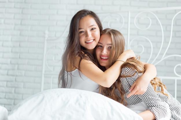 Twee mooie jonge vrouwen in bedpyjama'spartij