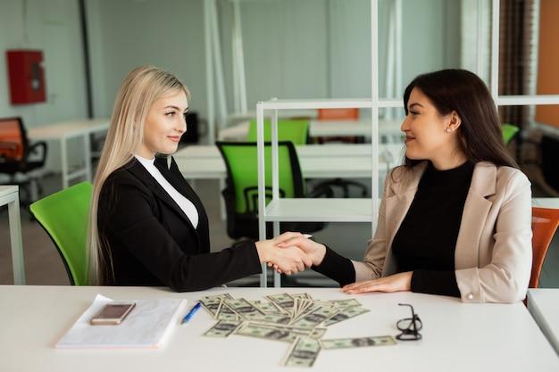 Twee mooie jonge vrouwen in het kantoor aan de tafel handen schudden
