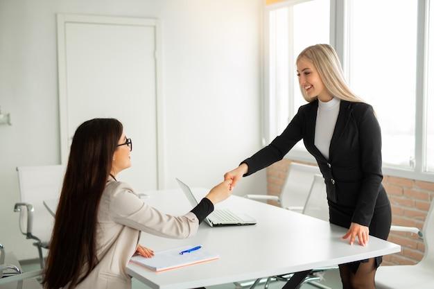 Twee mooie jonge vrouwen in het kantoor in pakken schudden elkaar de hand