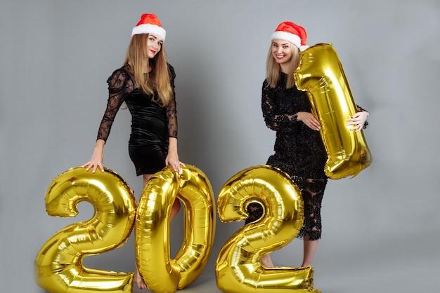 Twee mooie jonge vrouwen in kerstman-hoeden met 2021 gouden ballonnen op grijze achtergrond.