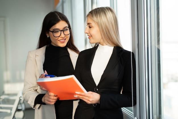 Twee mooie jonge vrouwen in pakken op kantoor