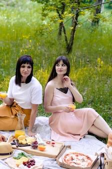 Twee mooie jonge vrouwen in park buiten op zonnige dag