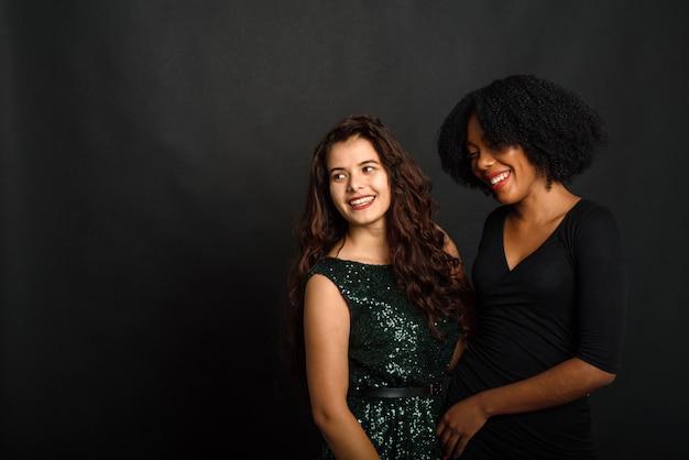 Twee mooie jonge vrouwen in prachtige avondjurken staan op een zwarte achtergrond, knuffelen en lachen.