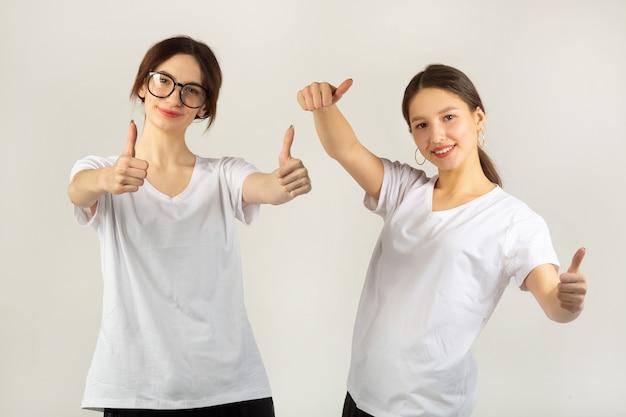 Twee mooie jonge vrouwen in witte t-shirts op een witte achtergrond met een handgebaar