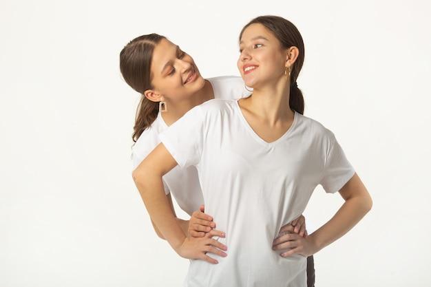 Twee mooie jonge vrouwen in witte t-shirts op een witte achtergrond