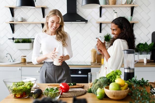 Twee mooie jonge vrouwen maken gezond ontbijt en glimlachen speels dichtbij het lijsthoogtepunt van verse groenten op de witte moderne keuken