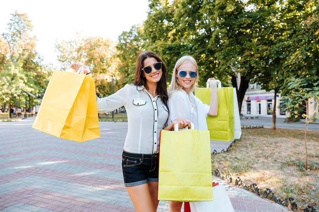 Twee mooie jonge vrouwen met boodschappentassen wandelen in de stad
