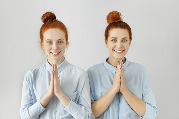 Twee mooie jonge vrouwen met soortgelijke kapsels van gemberknotjes, gekleed in lichtblauwe shirts
