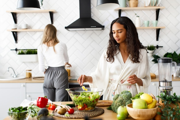 Twee mooie jonge vrouwen op de witte moderne keuken maken gezond ontbijt