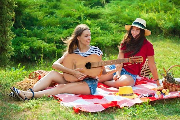 Twee mooie jonge vrouwen op een picknick die een gitaar speelt en pret heeft