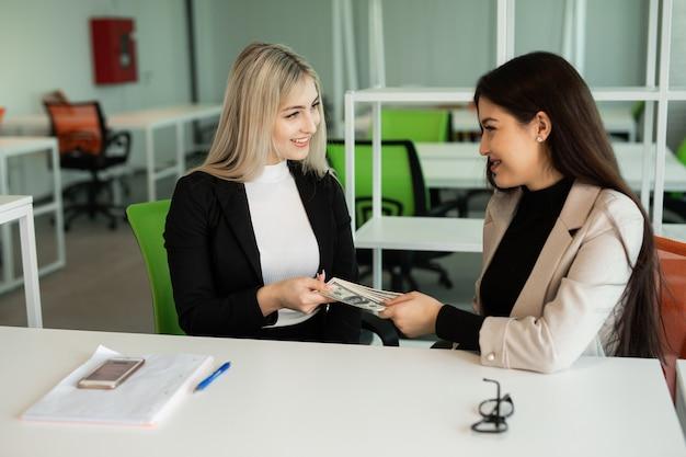 Twee mooie jonge vrouwen op kantoor aan tafel met dollars