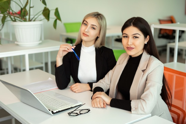 Twee mooie jonge vrouwen op kantoor aan tafel met een laptop