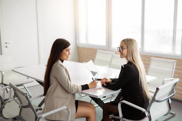 Twee mooie jonge vrouwen op kantoor aan tafel