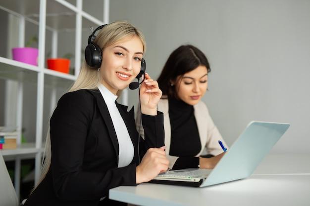 Twee mooie jonge vrouwen op kantoor met een laptop