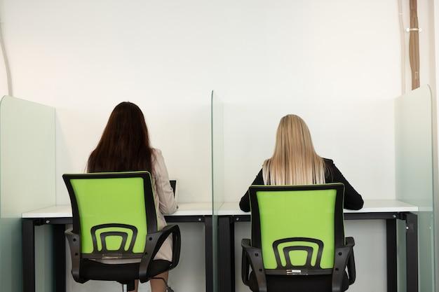 Twee mooie jonge vrouwen op kantoor zitten met hun rug aan de tafel