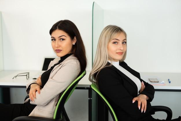Twee mooie jonge vrouwen op kantoor