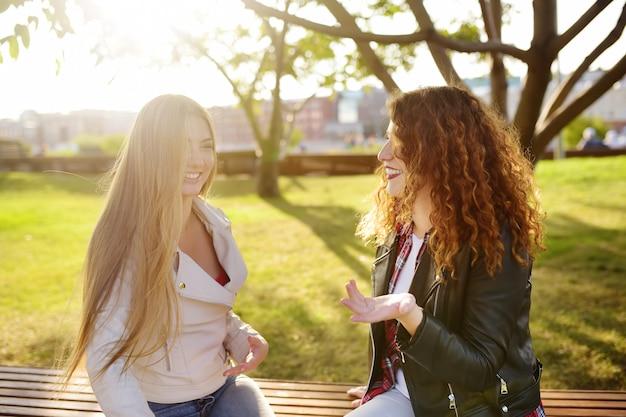 Twee mooie jonge vrouwen praten zittend op een bankje in zonnige park. communicatie en roddel.