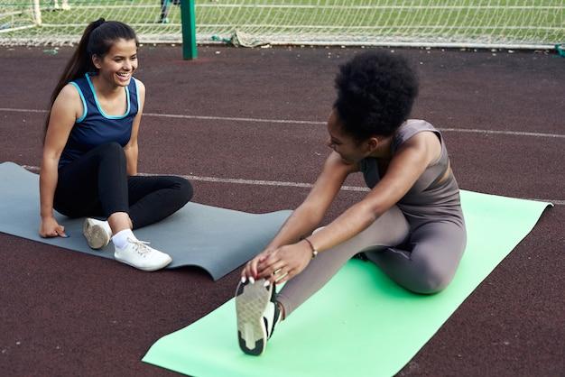 Twee mooie jonge vrouwen strekken zich uit terwijl ze op yogamatten zitten voordat ze buiten trainen. vriendinnen gaan sporten in het stadion.