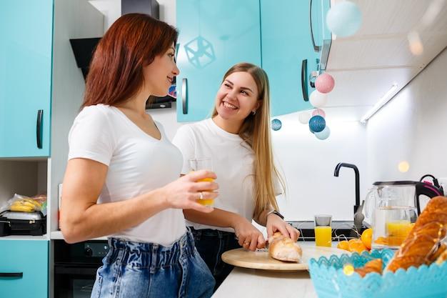 Twee mooie jonge vrouwenvrienden staan thuis aan de keukentafel en eten brood en drinken sinaasappelsap