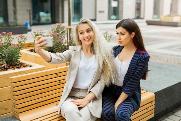 Twee mooie jonge vrouwtjes in pak worden aan de telefoon gefotografeerd