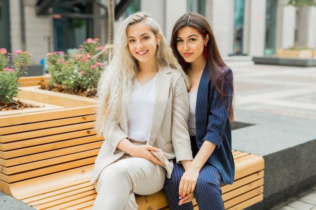 Twee mooie jonge vrouwtjes in zomerkostuums op een bankje