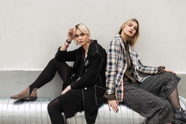 Twee mooie jonge zussen met blond haar met sexy lippen in vintage kleding in mode-laarzen ontspant op metalen pijp in de buurt van de muur in de stad
