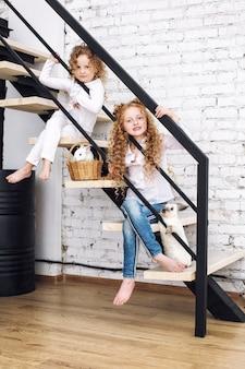 Twee mooie kindermeisjes met krullend haar en pluizige konijnen zitten op de trap