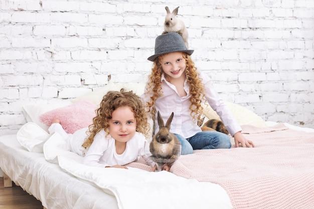 Twee mooie kindermeisjes met krullend haar en pluizige konijnen zitten thuis op het bed