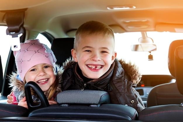 Twee mooie kleine kinderenjongen en meisje in een autobinnenland