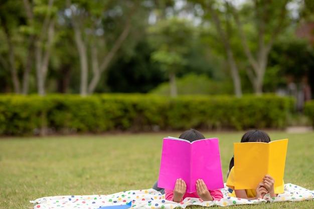 Twee mooie kleine meisjes die boeken lezen in de tuin, zittend op het gras. het concept van onderwijs en vriendschap.