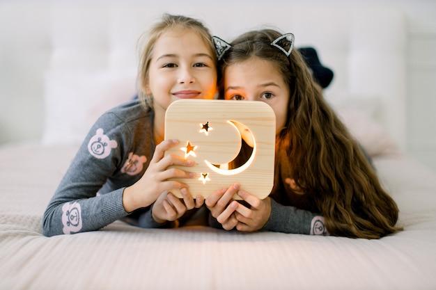 Twee mooie kleine meisjes zusjes, liggend op bed thuis en genieten van hun tijd spelen met houten nachtlampje met maan en sterren foto.