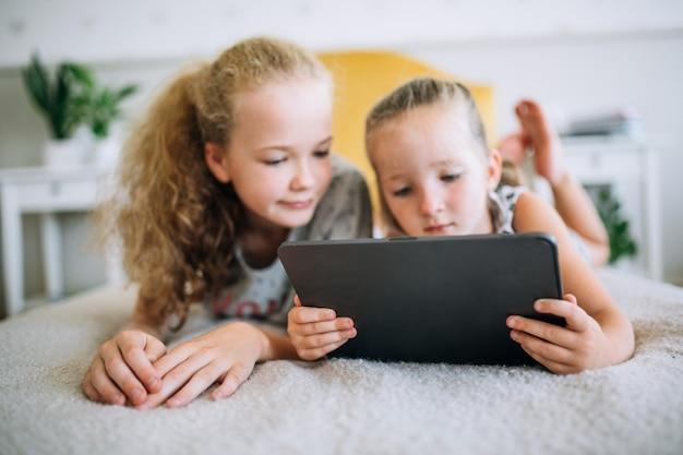 Twee mooie kleine zusjes die in bed liggen en naar het scherm van een tablet kijken, slimme kinderen die slimme technologie gebruiken